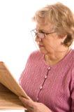 den gammalare tidningen läser kvinnan Royaltyfri Bild