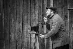 Den gammalmodiga fotografen frågar för ett leende Arbeten på kamera för stort format Idé - fotografi av 1930sen-1950s arkivbilder