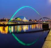 Den Gateshead milleniumbron och visa mannen på natten royaltyfri bild