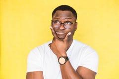 Den generade os?kra afrikansk amerikanmannen med exponeringsglas rymmer hans haka och sn?rper hans kanter, ser incredulously, f?r royaltyfria bilder
