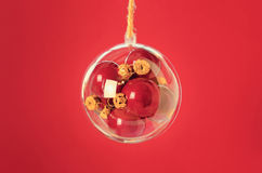 Den genomskinliga bollen med röd jul klumpa ihop sig inom på röd backgr Arkivbilder