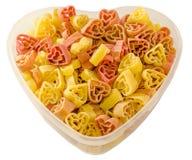 Den genomskinliga hjärtaformvasen (bunke) fyllde med kulör (rött, gulna en apelsin), hjärtaformpasta, vit bakgrund Royaltyfri Bild