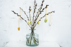 Den genomskinliga vasen med filialer dekorerade med träägg för easter Fotografering för Bildbyråer