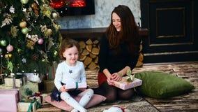 Den genral sikten av modern och dottern inom rummet med det Chrismas trädet och fullt av gåvor lager videofilmer