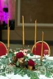 Den gifta sig tabellinställningen dekoreras med nya blommor i en mässingsbunke och guld- stearinljus i mässingsljusstakar br?llop royaltyfri foto