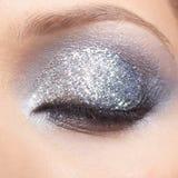 Den glänsande kvinnan synar makeup Royaltyfria Bilder