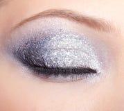 Den glänsande kvinnan synar makeup Arkivbild