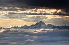 Den glödande solen rays ovanför snöig Julian Alps och havet av moln Royaltyfria Foton