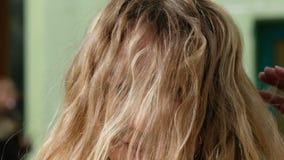 Den gladde och gladlynta flickan med blont lockigt hår som flyttar hennes huvud, och hennes hår svänger vänstert och högert arkivfilmer