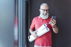 Den glade äldre gråhåriga affärsmannen använder mobiltelefonen royaltyfri bild