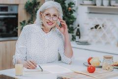 Den glade äldre kvinnan skriver recept under att laga mat arkivbilder