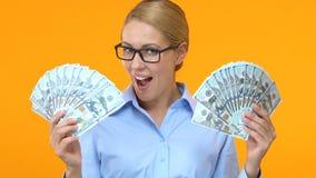 Den glade affärsdamen som visar grupper av dollar och säger, överraskar, startvinst arkivfilmer
