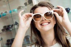 Den glade attraktiva brunetten som väljer nya par av solglasögon med hjälp av, shoppar assistenten, tillfredsställas med det nya  Royaltyfria Bilder
