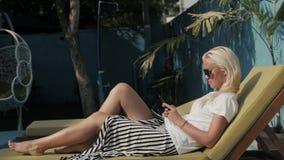 Den glade blonda flickan som kontrollerar post i samkväm, knyter kontakt, medan vänta vänner nära hotellet för att simma i pöl ti stock video