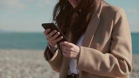 Den glade brunettkvinnan knackar lätt på på skärm av smartphonen på stranden, närbild lager videofilmer