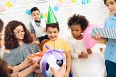 Den glade födelsedagpojken mottar fotbollbollen som födelsedaggåvan lycklig deltagare för födelsedag royaltyfria foton