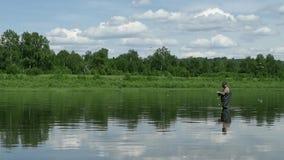 Den glade fiskaren fiskar i lugna flodvatten nära kusten arkivfilmer