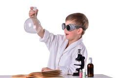Den glade forskarepojken i den vita ämbetsdräkten och svarta exponeringsglas rymmer en tom flaska Arkivfoto