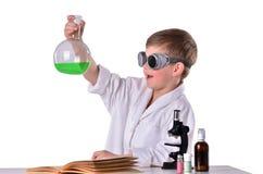 Den glade forskarepojken i svarta exponeringsglas rymmer en flaska med grön flytande inom Arkivfoton