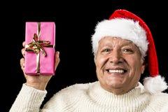 Den glade gamala mannen som ställer ut en rosa färg, slogg in gåva Royaltyfri Bild