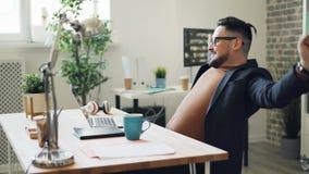 Den glade grabben som använder bärbara datorn som kopplar av därefter le att tycka om, vilar i arbetsplats arkivfilmer
