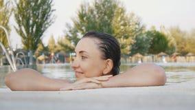 Den glade gulliga kvinnan tycker om vatten som lägger hennes huvud på hennes händer på poolsiden lager videofilmer