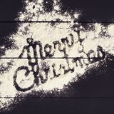 Den glade julen för inskrift som är skriftlig med mjöl på en mörk träbakgrund kortjul som greeting Arkivfoto