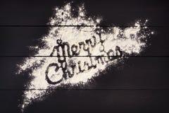 Den glade julen för inskrift som är skriftlig med mjöl på en mörk träbakgrund kortjul som greeting Arkivbilder
