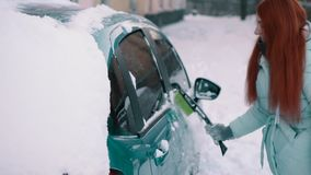 Den glade kvinnan gör ren snö från hennes bil stock video
