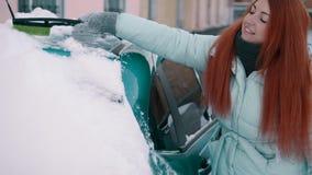 Den glade kvinnan gör ren snö från hennes bil lager videofilmer