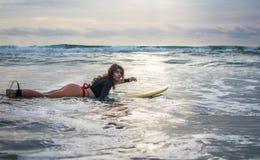 Den glade kvinnan har in gyckel, innan han surfar Surfareflicka med vita linjer maskering på hennes nätta bräde för framsidahållb royaltyfria bilder