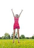 Den glade kvinnan hoppar i smörblommaäng Arkivfoto