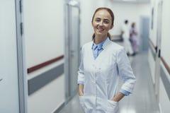 Den glade kvinnliga allmänna praktiker tycker om arbete i klinik royaltyfri bild
