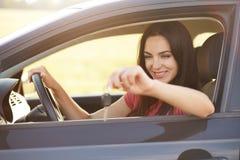 Den glade kvinnliga chauffören rymmer tangenter från bilen som går att sälja den, annonserar den snabba bilen och att vara i det  royaltyfri foto