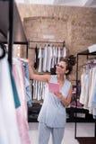 Den glade kvinnlign shoppar assistenten som kontrollerar kläderformat fotografering för bildbyråer