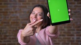 Den glade le caucasian brunettkvinnan visar närbildgräsplanskärmen på minnestavlan och använder hennes apparat, medan stå arkivfilmer