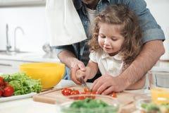 Den glade lilla flickan är involverad i matlagningprocess med pappa royaltyfria foton