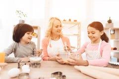 Den glade lilla flickan slår ägg i bunke med mjölkar, och hennes broder häller mjöl royaltyfria bilder