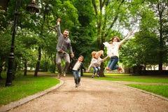 Den glade lyckliga familjen i sommar parkerar tillsammans att hoppa har gyckel royaltyfri fotografi
