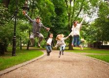 Den glade lyckliga familjen i sommar parkerar tillsammans att hoppa har gyckel fotografering för bildbyråer