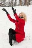 Den glade nätta flickan kastar upp snö Fotografering för Bildbyråer