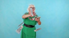 Den glade positiva äldre kvinnan kastar pappers- sedlar på en blå bakgrund långsam mo stock video