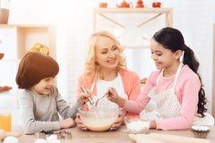Den glade pysen slår ägg i bunke med mjölkar, och hennes syster häller mjöl arkivfoton