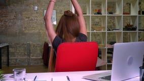 Den glade röda caucasian flickan dansar, medan sitta lyckligt och vända på cirkeln i stol nära hennes dator och skrivbord lager videofilmer