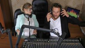 Den glade den radiovärdsmannen och kvinnlign talar in i mikrofonen nära ljudsignal blandare på studion stock video