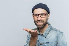 Den glade skäggiga mannen i moderiktig eyewear uttrycker hans förälskelse, visar ai arkivfoton