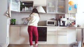 Den glade unga härliga kvinnan dansar i bärande pyjamas för kök, och hörlurar dricker en kopp kaffe i morgonen stock video