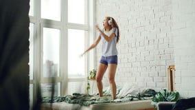 Den glade unga kvinnan dansar på hemmastadd bärande hörlurar för säng och tycker om musik Dubbelsäng tegelstenvägg som är panoram lager videofilmer
