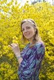Den glade unga kvinnan mot bakgrunden av den blomstra forzitionen St?ende royaltyfria foton