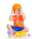 Den gladlynt barnpojken med den hårda hatten leker med byggande kvartertoys Arkivfoton
